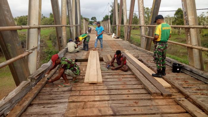 Bersama Warga Kampung Toray, Satgas Yonif Mekanis Raider 411/Divif 2 Kostrad Bergotong Royong Perbaiki Jembatan