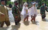 Banjir Menggenangi Benjeng Tidak  Menyurutkan Babinsa Koramil 0817/10 Benjeng Mendampingi Calon Penganten Menuju Kantot KUA